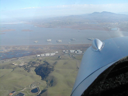Approaching the mothballed WW2 battleships in Suisun Bay, visible off the left of the plane's nose