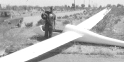 The object being displayed by yours truly is the actual landing gear (wheel assembly) of the aircraft, which had just been forcibly torn out of the glider due to landing on a road near Cantil, CA which was about five feet narrower than the airplane's wingspan.